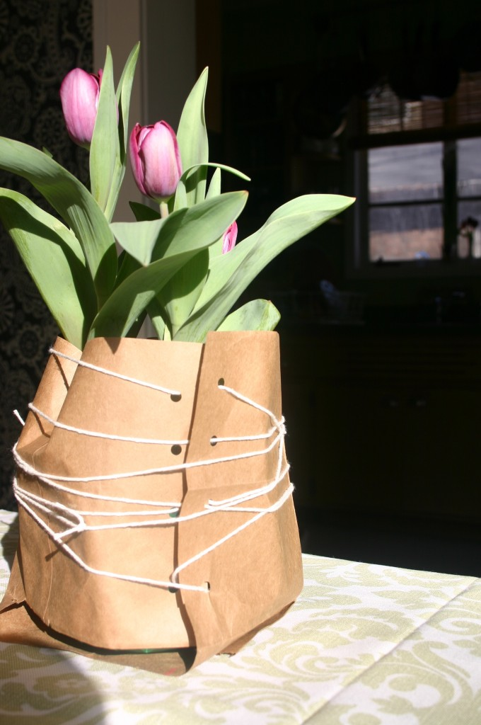Potted tulips in brown bag wrapping.