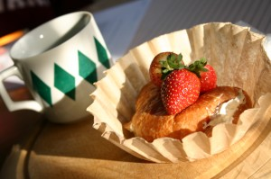 A croissant with cream cheese and strawberries on top served up on an ubleached coffee filter.
