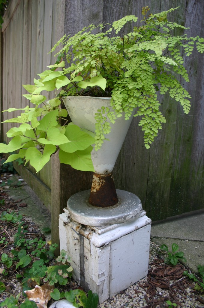 An umbrella stand is repurposed as a planter; it sits on the top of an old post. Combining the two pieces gave me the height I desired.