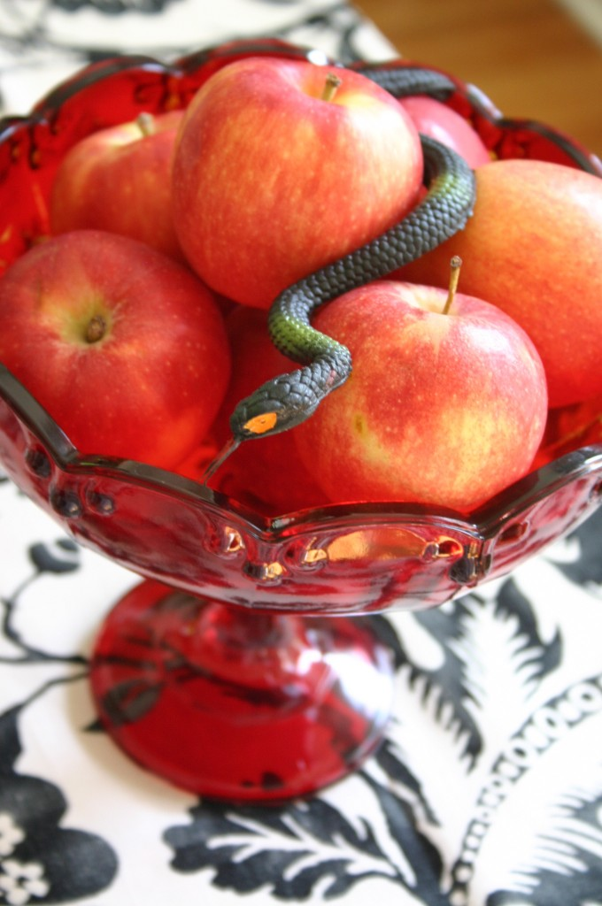 This red glass footed bowl holds apples and a rubber snake.