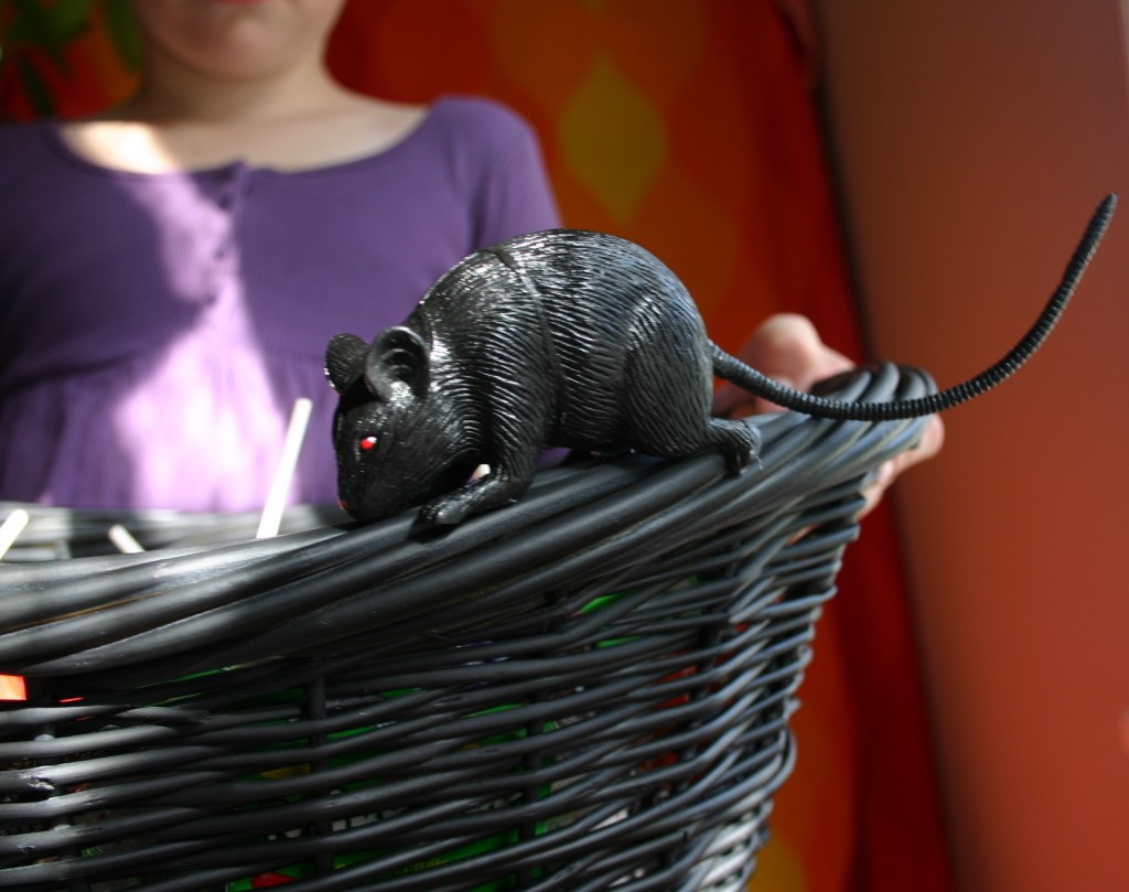 A rubber rat purchased at a Halloween supply store is hot-glued onto the edge of the basket.