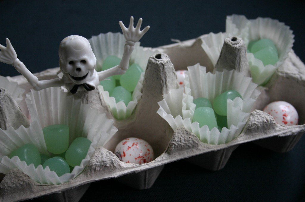 An unpainted egg carton filled with Ghost Dots and Eyeball Gumballs and topped off with a skeleton finger puppet.