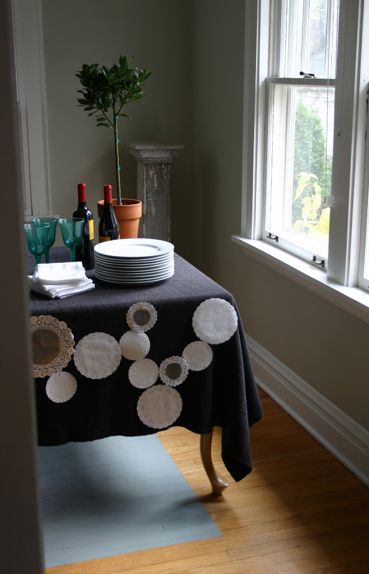 Silver and white paper doilies of varying sizes are stapled together to create a lacey tabletop cover for a winter dinner.