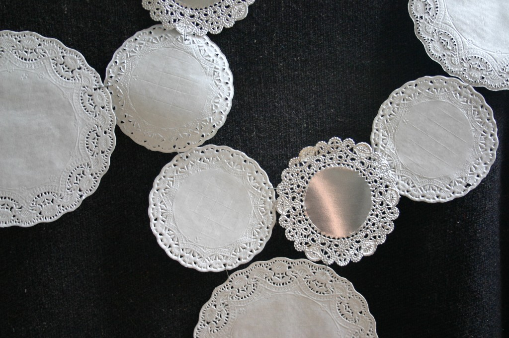 Staple edges together to create a design of your liking and attach to your tablecloth with doublesided tape. Doilies can be purchased at craft and party stores.