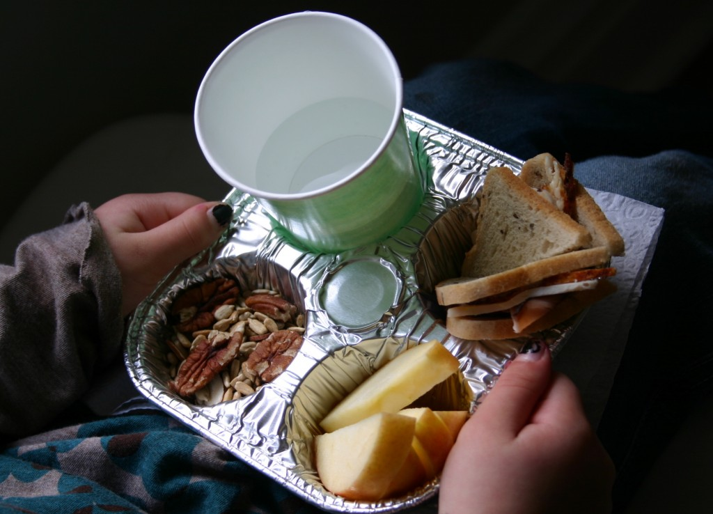 A foil cupcake tin with four sections holds apple slices, trail mix, a small turkey sandwich - made from cocktail rye bread - and a cup of water. This makes a perfect compartmentalized tray for small laps. For breakfast- try using  a hard-boiled egg, mini bagel and orange sections.