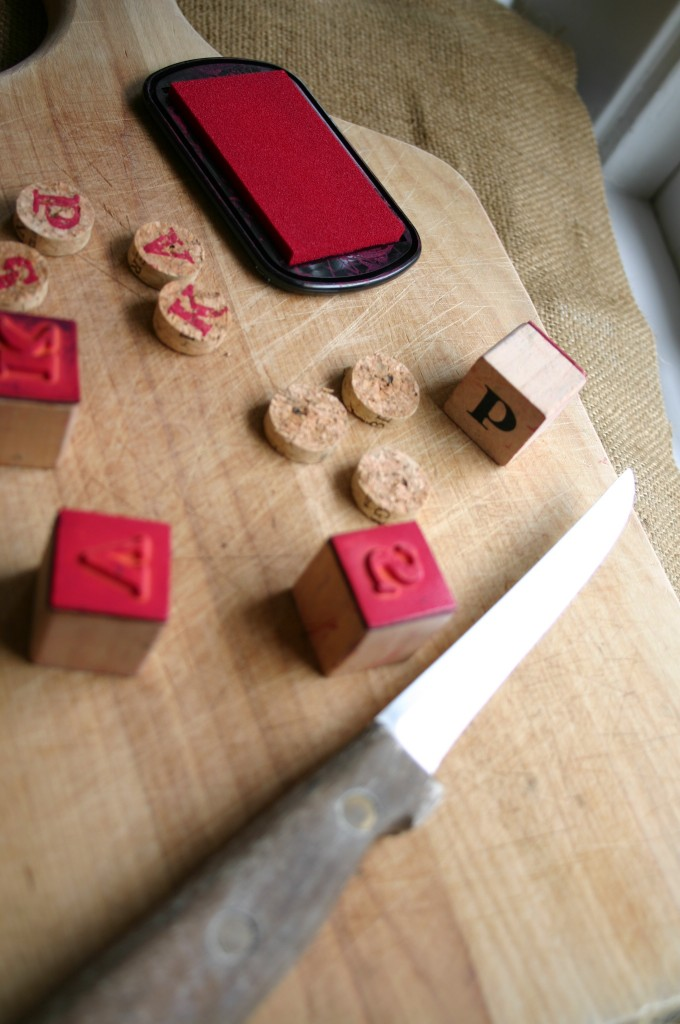 Using a sharp knife and a cutting board - cut the cork into 1/2 inch discs. Stamp each cork slice with a letter rubber stamp.