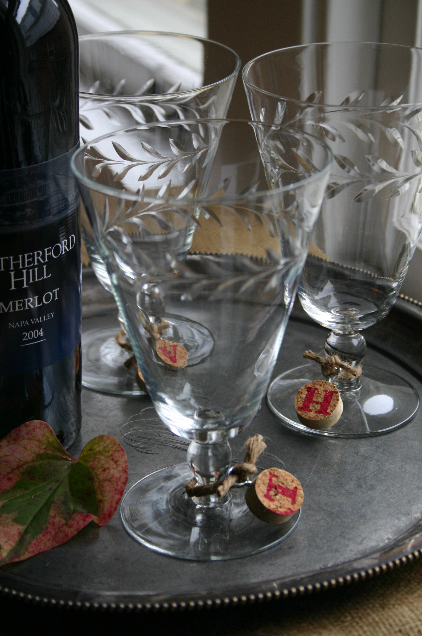 Wine corks, cut into half inch thick discs and rubberstamped with a letter are attached to the stem of a wine glass with jute.
