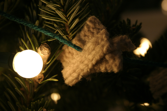 Bits of an old sweater are clipped into small squares and strung on yarn to make a soft, textured garland.