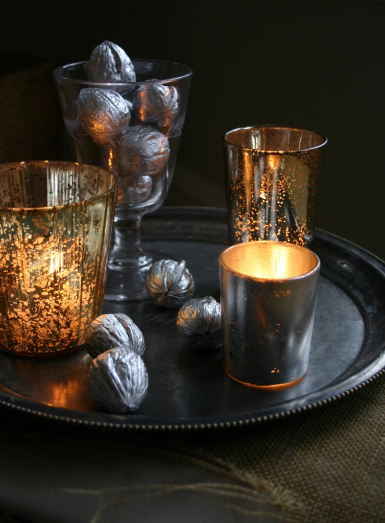 Walnuts, spray painted silver, mix in among pewter and silvered glass votives to create a glimmering centerpiece.