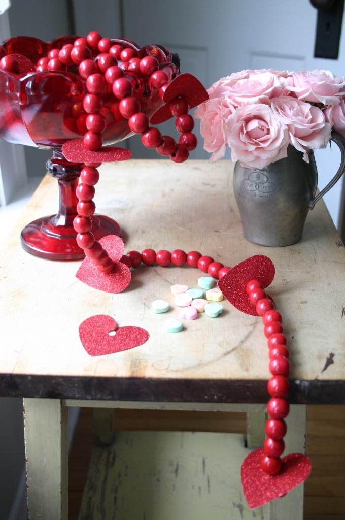 Red wooden beads make a wonderful Valentine's Day garland with the addition of a few more of those glittery paper hearts.
