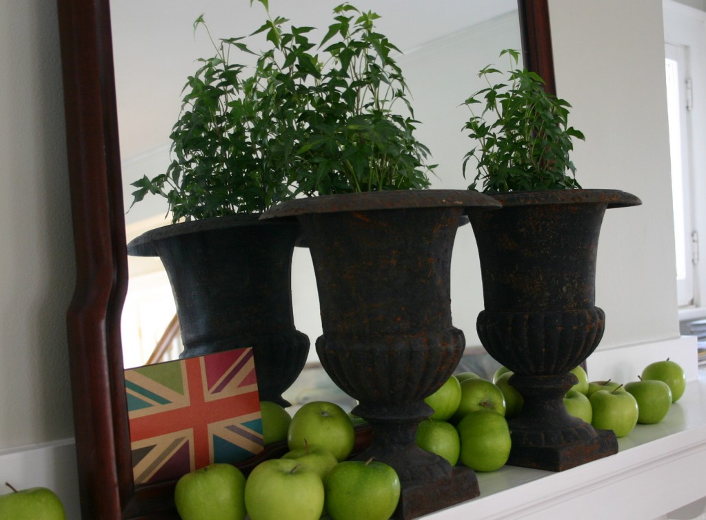 My mantel - several green apples spill out around two urns filled with ivy.