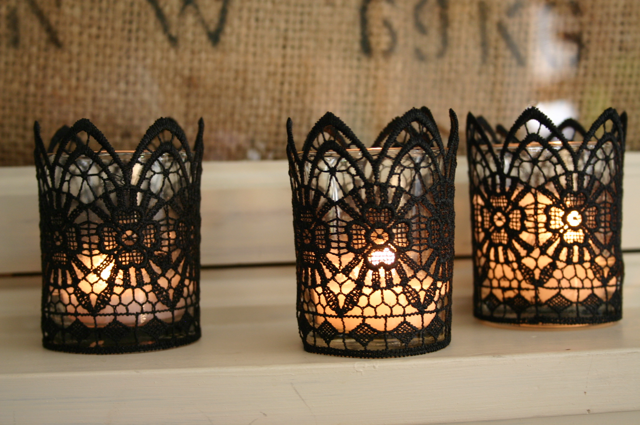 Simple glass votives are wrapped in black lace - these have a gothic feel to them, perfect for Halloween.