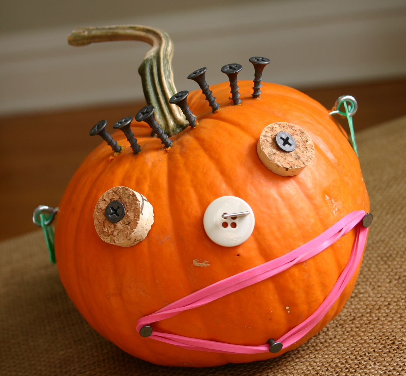 This project is great for little ones - there's no carving involved. A small pumpkin is given a face with the use of screws, buttons, slices of cork, rubber bands and plastic bread bag clips.