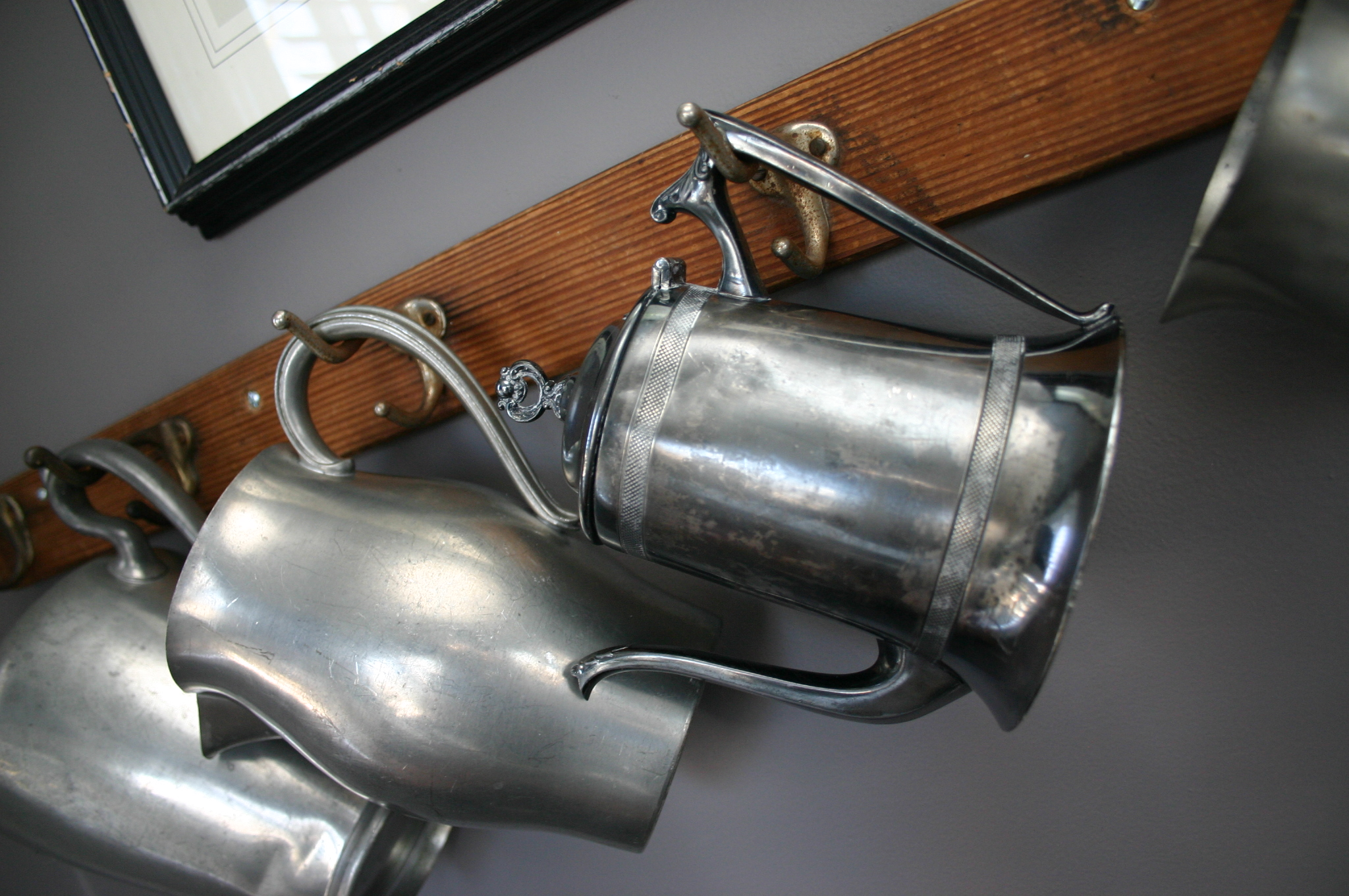I love pewter and silverplated pitchers. I cannot pass one up at a resale shop. Instead of displaying them all on one flat surface, I chose to hang them from hooks in our music room.