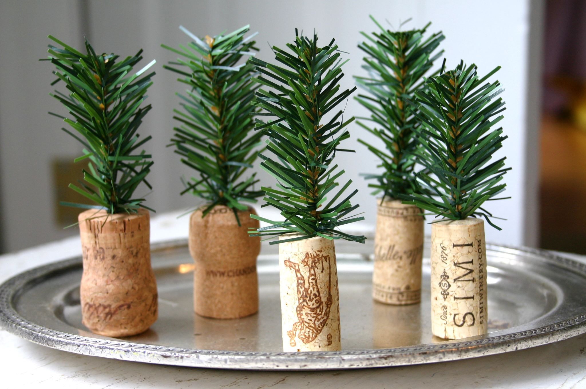 Clippings from artificial garland are stuck into wine and champagne corks to decorate a festive holiday table.