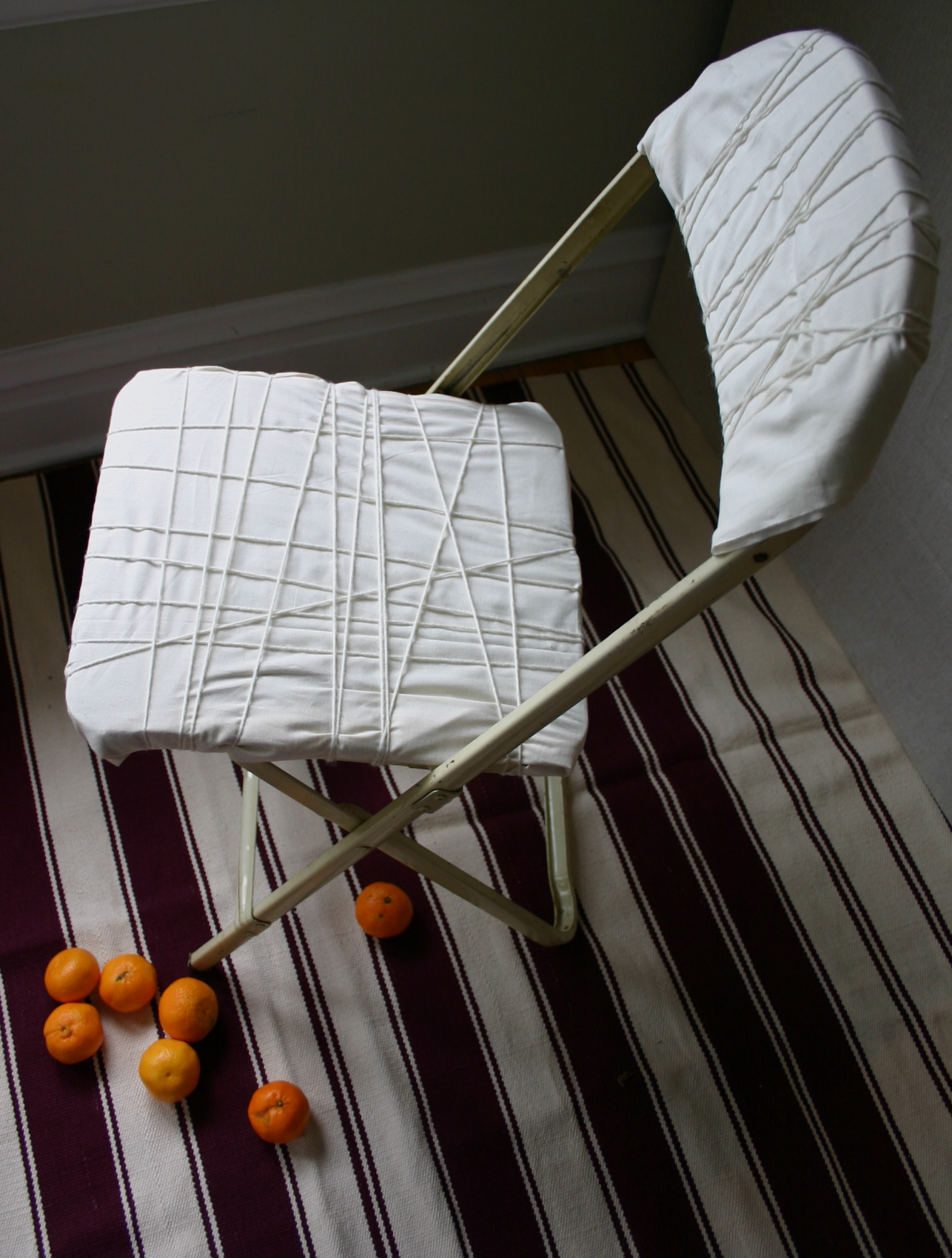 Entertaining a large crowd can leave me short on seating. Here I have transformed a $2.00 resale shop folding chair into a more stylish extra seat using muslin, yarn and rubber bands.