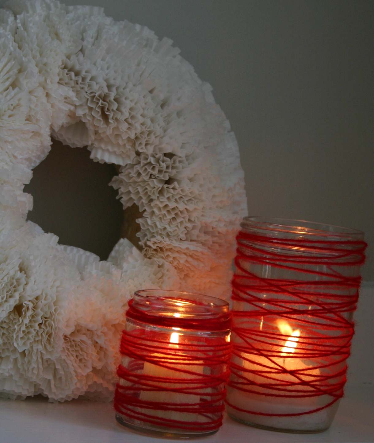 Jars are wrapped in red yarn to create simple & festive lighting for Valentine's Day - another easy craft for kids.