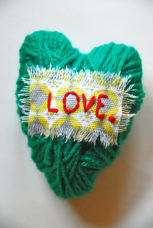 Tin foil is shaped into a heart, wrapped in yarn and given a tattered message of love.