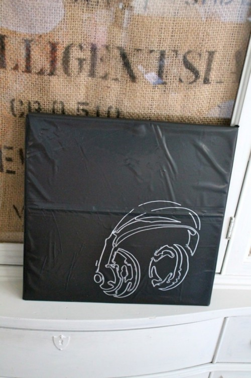 An Arctic Monkeys album is wrapped in a black garbage bag (thought it looked like leather) and stenciled with a metallic paint pen.