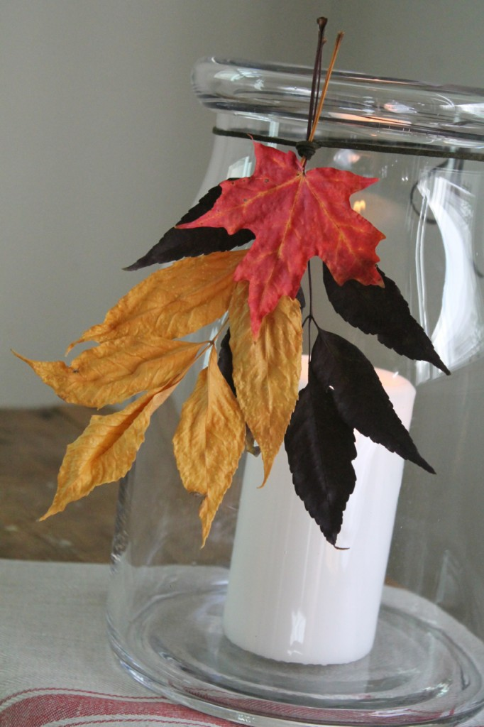 Collect leaves from outdoors. Press in a book for a few days. This will help to preserve the leaf. Arrange leaves in a bundler, tie together with a leather cord, tie around mouth of large jar.