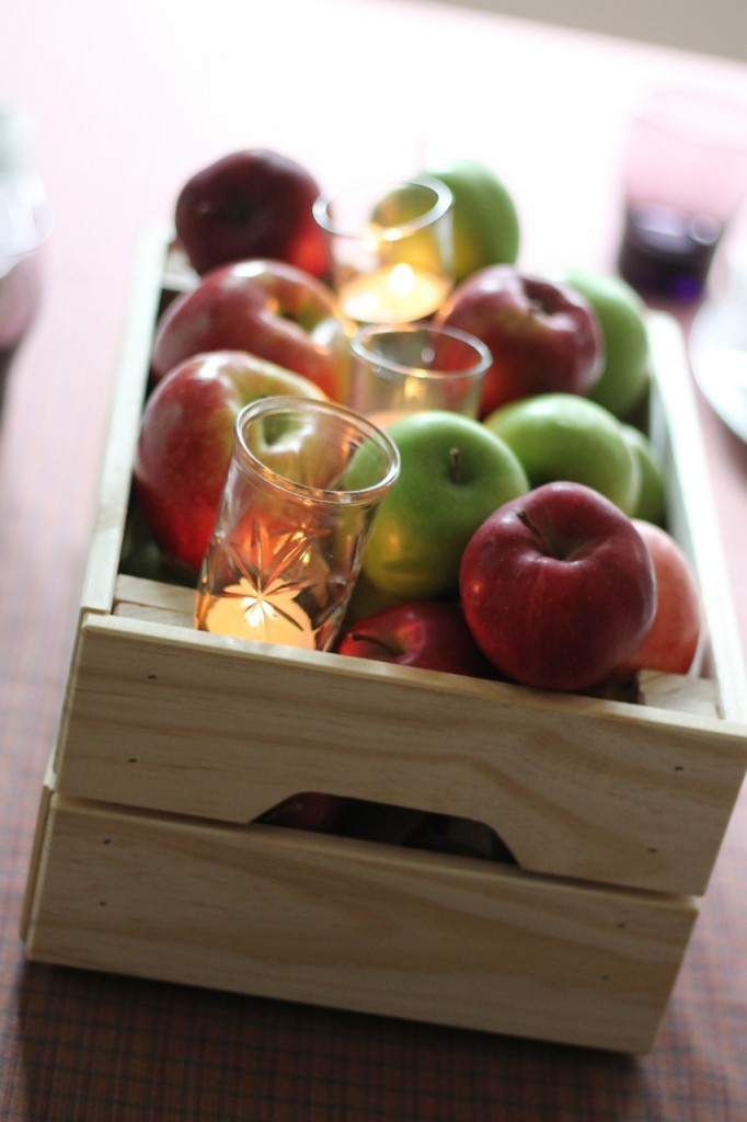 Two bags of apples are placed in a wooden crate, glass votives are nestled in.
